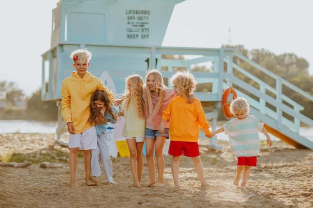 Zes kinderen in zomerkleren poseren op het zandstrand met blauwe badmeestertoren op de achtergrond