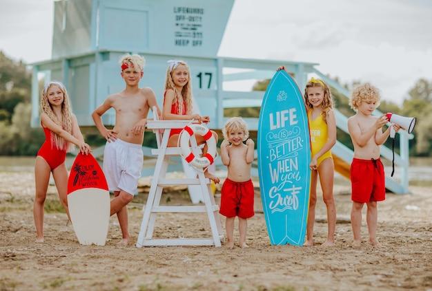 Zes kinderen poseren op het strand met blauwe surfplank en reddingsboei