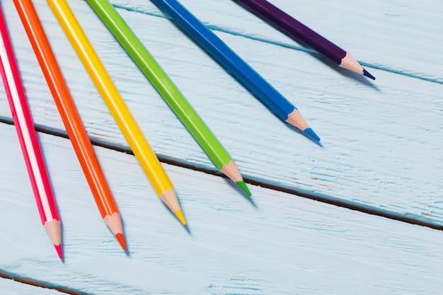 Zes kleuren regenboog van potloden op blauwe houten achtergrond