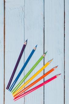 Zes-kleuren regenboog van potloden op blauwe houten tafel