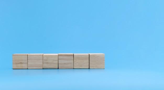 Zes lege houten kubusblokstapel op blauwe achtergrond met exemplaarruimte voor invoertekst en pictogram, tendens, creatief idee, financiën, strategie, zaken, online marketingconcept