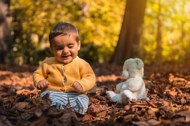 Zes maanden oude baby zit in de bladeren van de bomen met een witte beer in het park op een herfstzonsondergang. natuurlijke verlichting