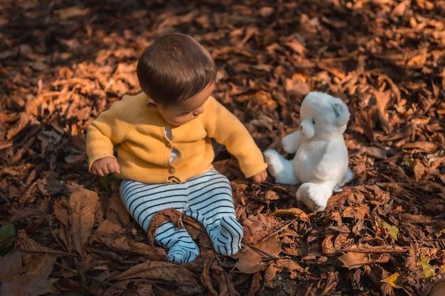 Zes maanden oude baby zit in de bladeren van de bomen met een witte teddybeer in het park op een herfstzonsondergang