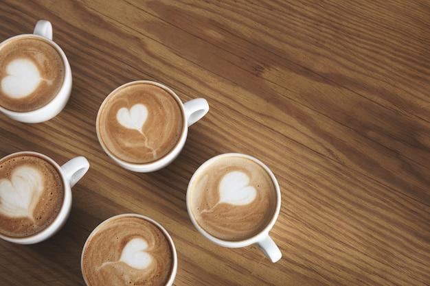 Zes mooie witte ceramische kopjes met cappuccino die op houten lijst wordt geïsoleerd. schuim bovenop in vliegende hartvorm