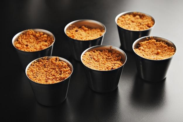 Zes porties appelkruimeltaart in individuele stalen bekers op glanzend zwarte tafel