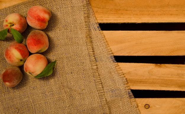 Zes rijpe perziken met bladeren op zak en houten platen, plaats voor tekst, bovenaanzicht