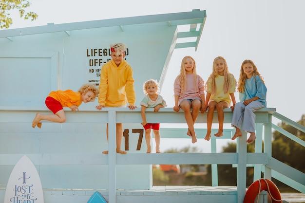 Zes schattige blonde kinderen in kleurrijke kleding poseren samen op de badmeestertoren op het strand