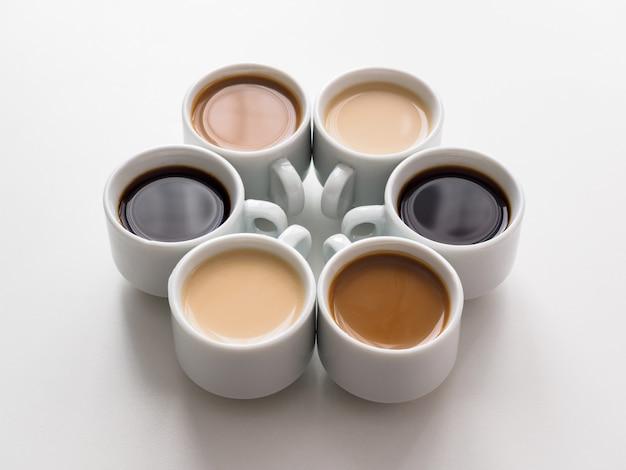 Zes verschillende kopjes koffie op een witte tafel. het uitzicht vanaf de top. witte koffieset