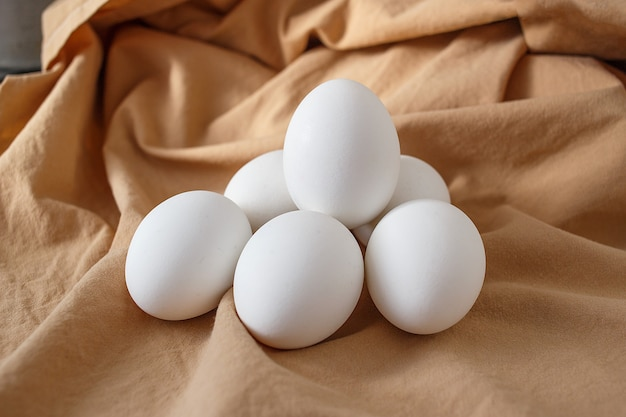 Zes witte kippeneieren op beige achtergrond