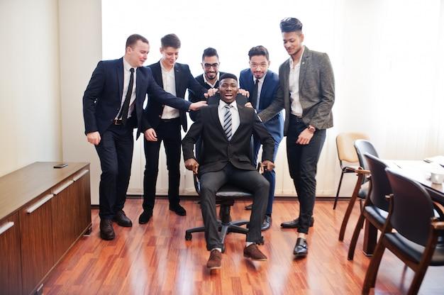 Zes zakenmannen permanent op kantoor en man op stoel