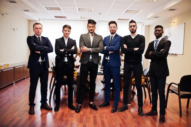 Zes zakenmannen permanent op kantoor met gekruiste armen