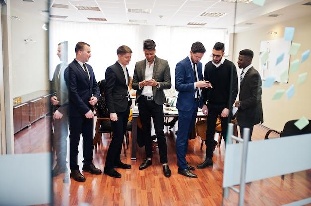Zes zakenmannen staan op kantoor en gebruiken mobiele telefoons