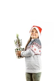Zesjarig kaukasisch meisje in witte kersttrui met rendieren en kerstmanhoed met kleine...
