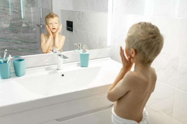Zesjarige jongen brengt aftershave aan zoals papa 's ochtends in bad, hygiëne in de ochtend