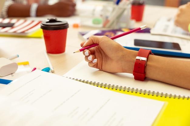 Zet de verbeelding aan. close-up van een vrouwelijke hand die een potlood vasthoudt tijdens het voltooien van de taaltest