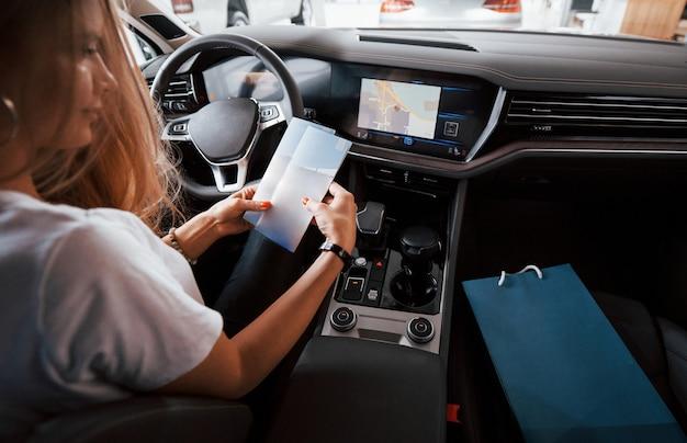 Zet hier uw tekst. meisje in moderne auto in de salon. overdag binnenshuis. een nieuw voertuig kopen