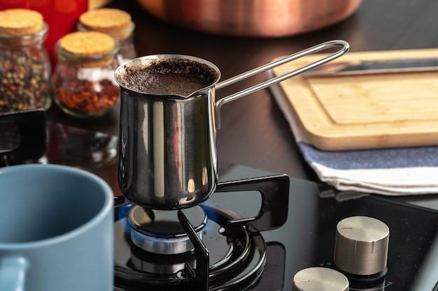 Zet koffie in een staal turk op een gasfornuis