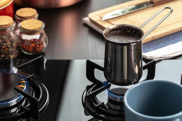 Zet koffie in een stalen turk op een gasfornuis van dichtbij