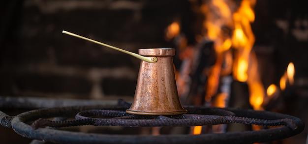 Zet koffie in een turk op open vuur. het concept van een gezellige sfeer en drankjes.