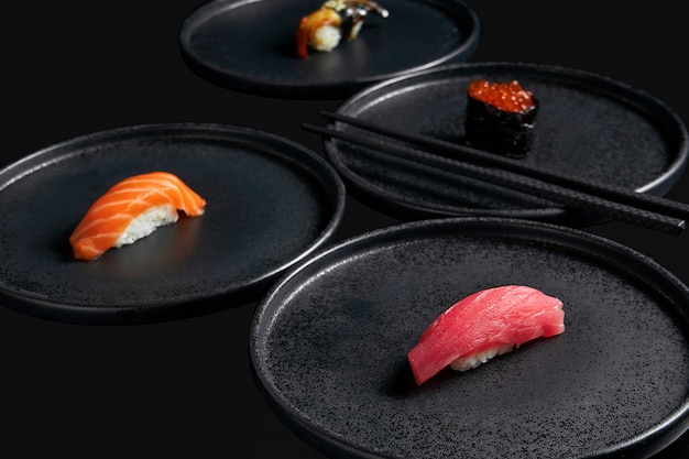 Zet sashimi sushi met tonijn, zalmkaviaar, zalm en gerookte paling op stijlvolle zwarte keramische borden op een zwarte ondergrond. japanse traditionele keuken. foto voor het menu