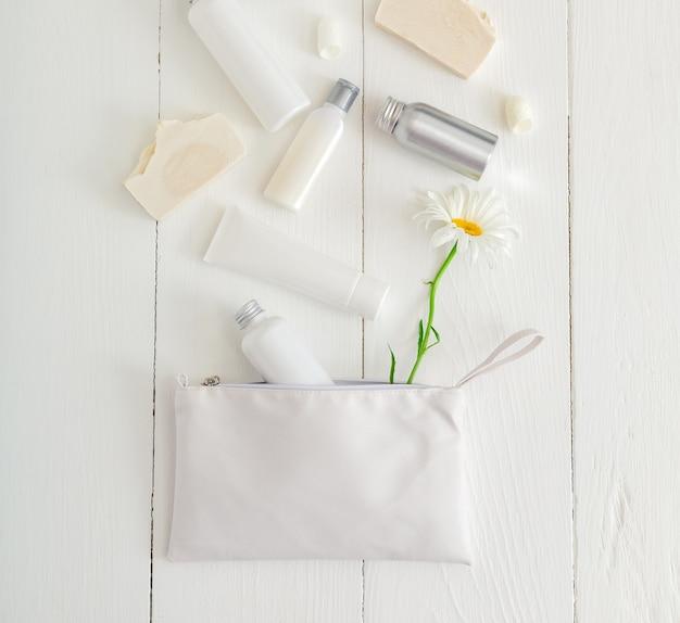 Zet witte cosmetische producten op houten tafel met bloemen in make-uptas. schoonheid huidverzorging haarbehandeling cosmetische serum olie vochtinbrengende crème huidcrème body butter zeep lotion shampoo. plat leggen.