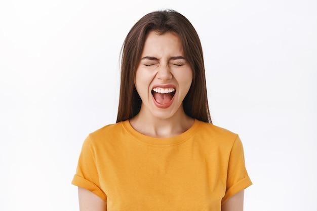 Zeurende humeurige vriendin schreeuwt of klaagt luid, staat ontevreden, bang om spin in de badkamer te zien, schreeuwt met gesloten ogen en volledig geopende mond, staande witte achtergrond