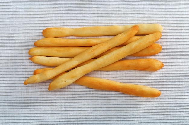Zeven broodstokken die op katoenen tafelkleed liggen.