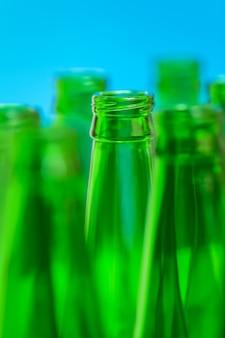 Zeven groene flessenhalzen op blauwe achtergrond, in centrum één fles in nadruk.