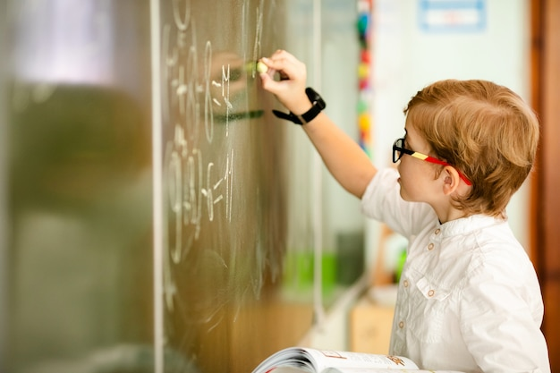 Zeven jaar oud kind dat met glazen zijn huiswerk op school schrijft