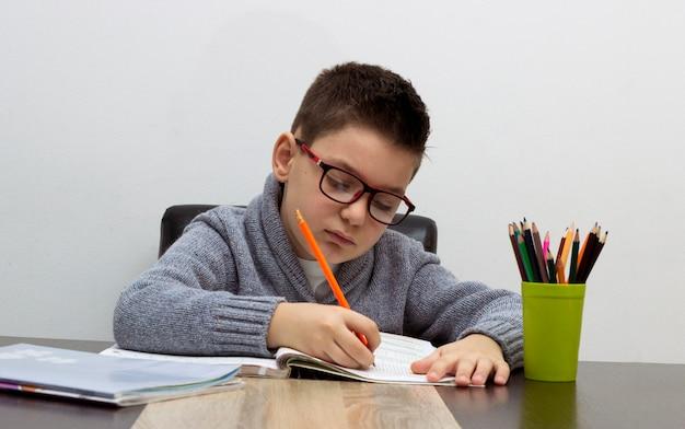 Zeven jaar oud kind thuis schrijven. jongen studeert aan tafel. kid tekening met een potlood.