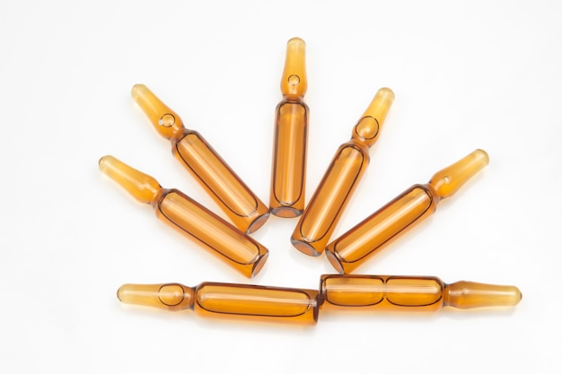 Zeven medische glasampullen voor injectiedrug op een witte achtergrond