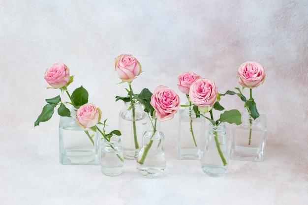 Zeven rozen in verschillende soorten vazen