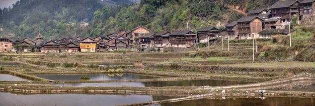 Zhaoxing dong village, provincie guizhou, china panoramisch uitzicht van etnische minderheden in het zuidwesten van china, houten hutten op de achtergrond van bergen, in de buurt van rijstvelden, lente.