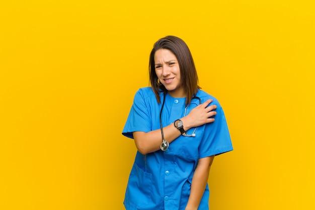 Zich angstig, ziek, ziek en ongelukkig voelen, lijden aan een pijnlijke buikpijn of griep geïsoleerd tegen de gele muur