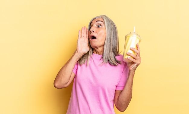 Zich blij, opgewonden en verrast voelen, opzij kijken met beide handen op het gezicht en een milkshake vasthouden