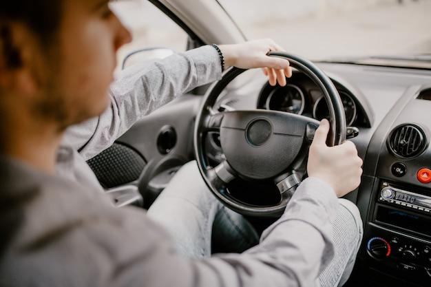 Zich concentreren op de weg. achtermening van de jonge knappe mens die recht terwijl het drijven van een auto kijken