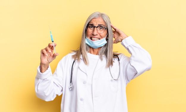 Zich gestrest, bezorgd, angstig of bang voelen, met de handen op het hoofd, in paniek raken bij een vergissing. dokter en vaccin concept