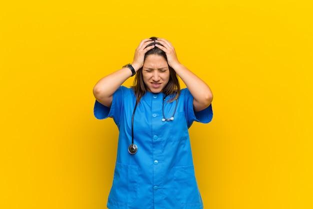 Zich gestrest en gefrustreerd voelen, handen opheffen, zich moe, ongelukkig voelen en met migraine geïsoleerd tegen een gele muur