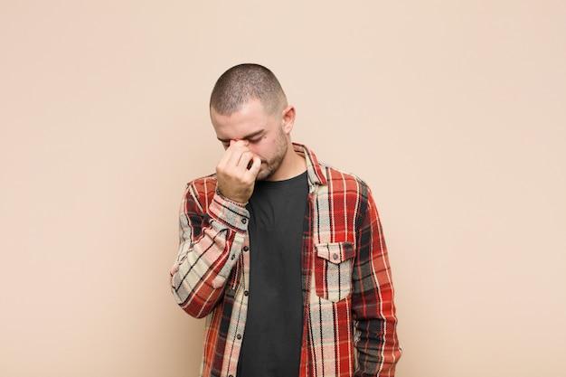 Zich gestrest, ongelukkig en gefrustreerd voelen, het voorhoofd aanraken en last hebben van migraine van ernstige hoofdpijn