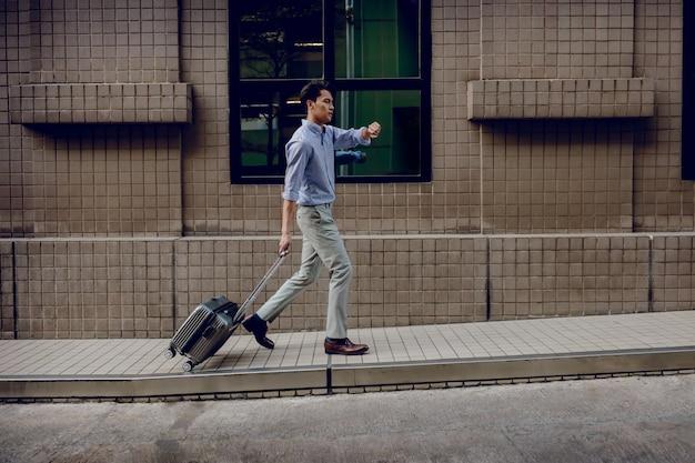 Zich haasten om op zakenreis te gaan. benadrukt passagier zakenman wandelen met koffer in de stad, bezorgd gezicht terwijl het zien van horloge.