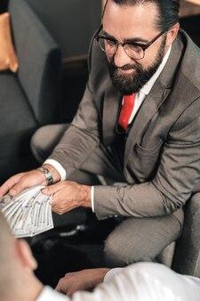 Zich illegaal gedragen. advocaat met baard die een bril draagt en zich illegaal gedraagt tijdens het ontvangen van steekpenningen van de cliënt