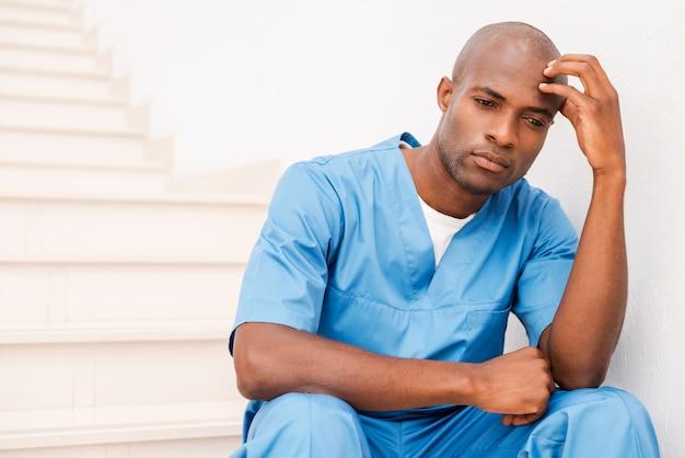 Zich moe en depressief voelen. depressieve jonge afrikaanse arts in blauw uniform die zijn hoofd met de hand aanraakt en wegkijkt terwijl hij aan de trap zit