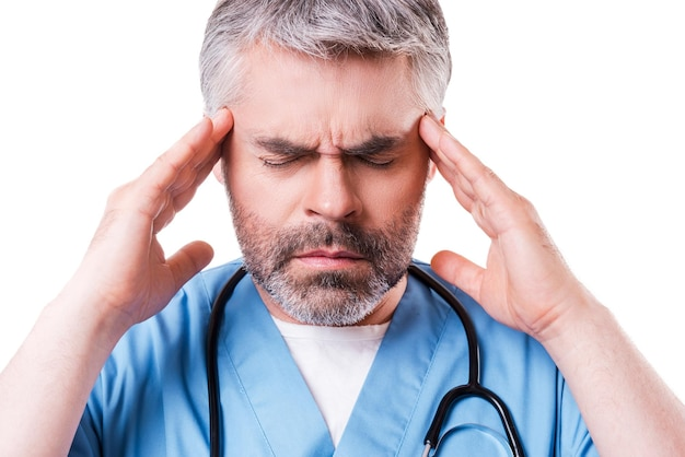Zich moe en gespannen voelen. depressieve volwassen chirurg die zijn hoofd met de handen aanraakt en de ogen gesloten houdt terwijl hij geïsoleerd op wit staat