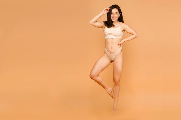 Zich mooi voelen. aantrekkelijke jonge vrouw in ondergoed glimlachend terwijl staande geïsoleerd op beige achtergrond.
