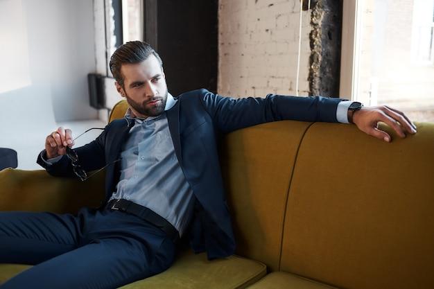 Zich ontspannen voelenelegante jonge en aantrekkelijke zakenman zit op de bank in zijn moderne kantoor en