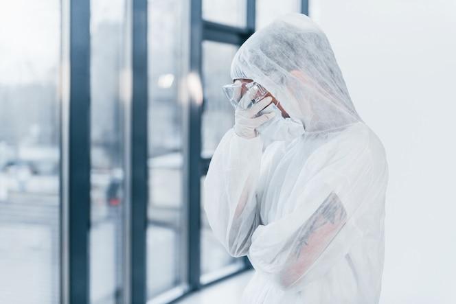 Zich slecht, moe en depressief voelen. portret van vrouwelijke arts wetenschapper in laboratoriumjas, eyewear verdediging en masker