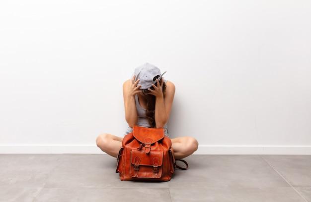 Zich verdrietig, gefrustreerd, nerveus en depressief voelen, het gezicht met beide handen bedekkend, huilend