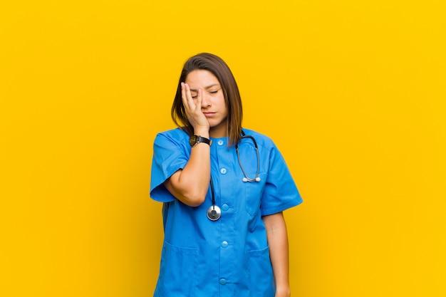 Zich verveeld, gefrustreerd en slaperig voelen na een vermoeiende, saaie en vervelende taak, gezicht met geïsoleerde hand vasthouden