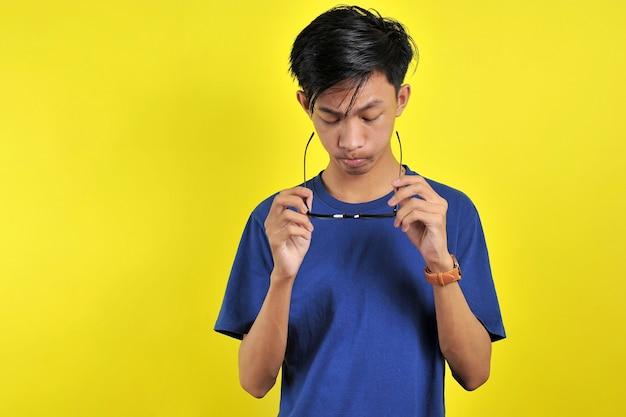 Zich vervelen, jonge aziatische man met een bril, geïsoleerd op gele achtergrond