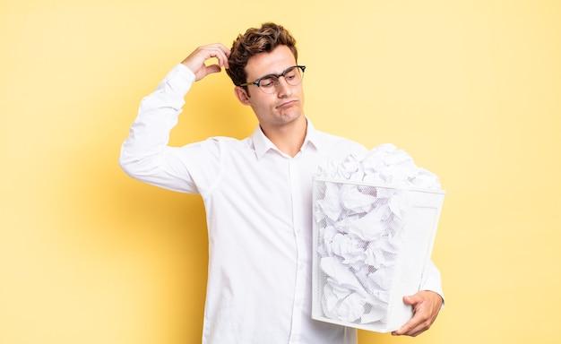 Zich verward en verward voelen, hoofd krabben en opzij kijken. prullenbak papier concept